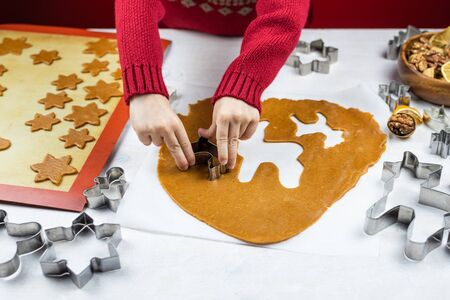 A child cuts a gingerbread cookie with a cookie cutter on a white background. Little mom's assistant.