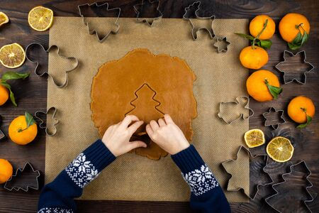 A child handstake out ginger cookies from rolled dough, cutter form a fir on a dark wooden background. Little mom's assistant. Christmas flat lay.