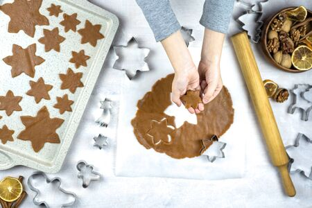 A child cuts a gingerbread cookie on a white background. Little mom's assistant. Hands holds cookie. Family Cooking flat lay.