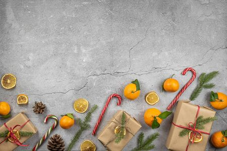Gifts wrapped in kraft paper and decorated with a spruce branch and dry orange. Christmas layout with sweets, mandarins and decor on a concrete background with copu space.