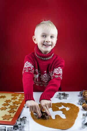 A child cuts a gingerbread cookie with a cookie cutter a snowflakes on a white background. Little cute mom's assistant.