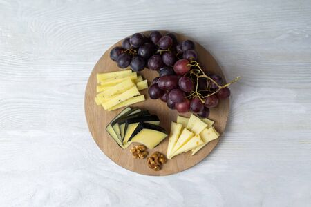 Three types of different cheese with additives are cut into pieces and laid out on a round wooden board. Nearby are grapes and walnuts. Flat lay on a white wooden table.