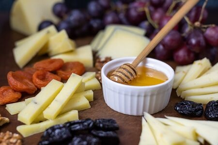 Close up photo of a board with sliced different types of cheeses with honey, grapes, nuts and dried fruits. A set of cheese plates for a party and guests on a dark background.