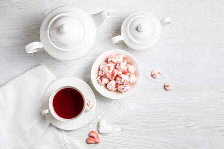 Beautiful romantic breakfast with red tea Hibiscus and meringue cookies in the shape of hearts and candys. White tea-set stand on a wooden table with a concrete background. Flat lay with copy space.