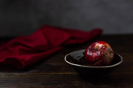 Art concept of the problem of food consumption. Red rotten apple on a plate with tehstil on a wooden table and a gray background. Minimalistic still life in a dark style of paintings by artists. Reklamní fotografie