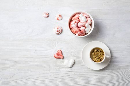 Beautiful romantic breakfast with coffee espresso and meringue cookies in the shape of hearts and candy. Standard-Bild - 140609589
