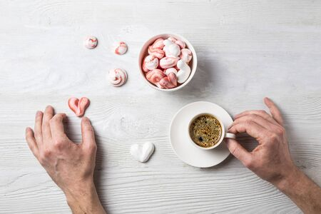 Romantic breakfast with coffee and meringue in the shape of hearts and candys. Mens hands holding a cup of espresso and a heart cookie. Cozy flat lay on a wooden table. Banque d'images - 140640115