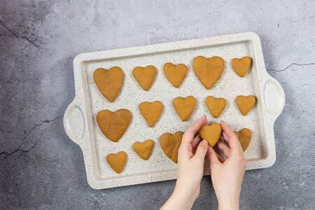 A womens hands hold a gingerbread a heart cookie on a concrete background with a baking tray. Flat lay cooking. Banque d'images