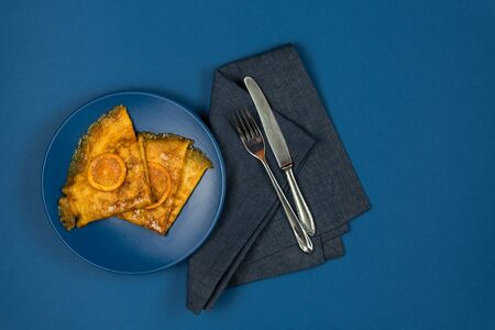 Two crepe suzette pancakes golden toasted with slices of orange and in syrup on a plate with cutlery on a napkin. On a paper background with a trendy blue classic color. Flat lay with copy place.