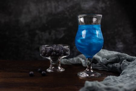 Sparkling glitter blue drink. A cocktail in a glass goblet stands on a wooden table with a transparent bowl of blueberries. Festive still life with copy space on a dark background. 写真素材