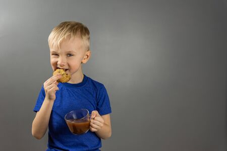 Cute cheerful blond boy eating homemade oatmeal cookies with a glass cup of cocoa. Happy sweet childhood. Portrait on a gray background with copy space.