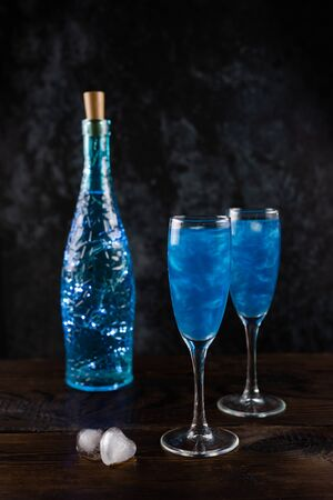 Sparkling glitter blue drinks. A champagne in two glasses stands on a wooden table with a luminous bottle and ice hearts. Festive vertical still life with copy space on a dark background.