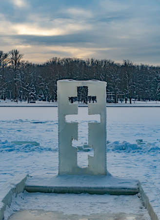 Ice sculpture in the shape of a cross next to the baptismal immersion font