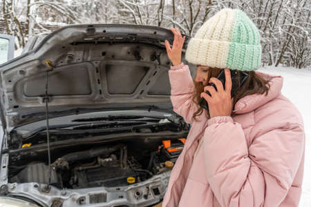Young brunette woman in a pink winter down jacket and warm hat is standing near a car with an open hood and talking on the phone