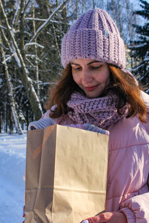 Woman holding gift packet with surprise, celebration