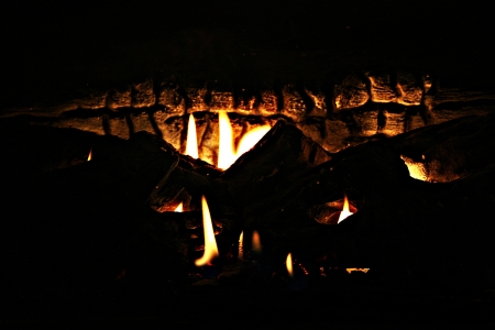 fire pit: beautiful fireplace flames light up the wood texture in the background