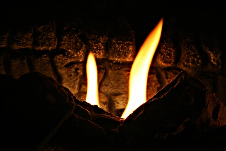 fire pit: 2 giant flames flickering among the depths of the fire pit make you feel like you are descending down into a well of fire Stock Photo