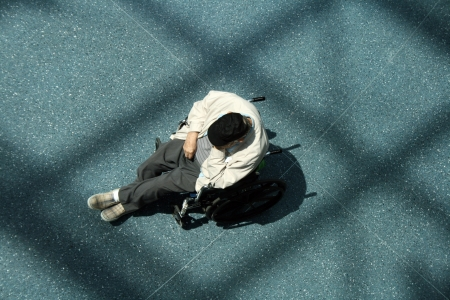 morose: Elderly man in wheelchair alone in a room as seen from above