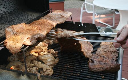 Meats cooking and being flipped on outdoor BBQ grill photo
