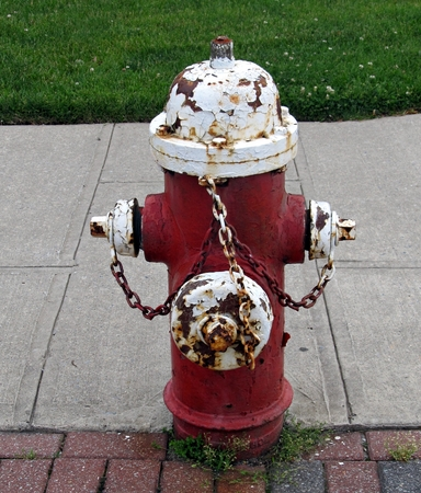 repaired: Close up image of an old fire hydrant in need of being repaired.  The paint is peeling off the hydrant and some specks of it can be seen on the ground if you look closely