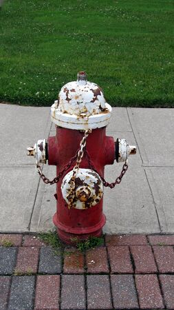 rusting: Full view of an old battered fire hydrant in need of new paint job as paint is peeling and hydrant is rusting Stock Photo