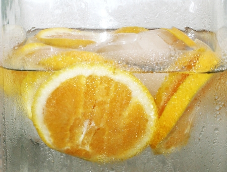 reach out: a close up image of a pitcher of freshly made orange infused water.  Fresh orange slices floating in ice cold water calling viewer to want to reach out for a refreshing drink