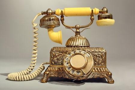 Old Victorian Style Telephone made of Brass and Plastic with Cord, Patinated and Scratched Stock Photo