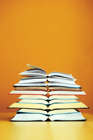 learned: Stack of Books on a Table  before Orange Wall  Stock Photo