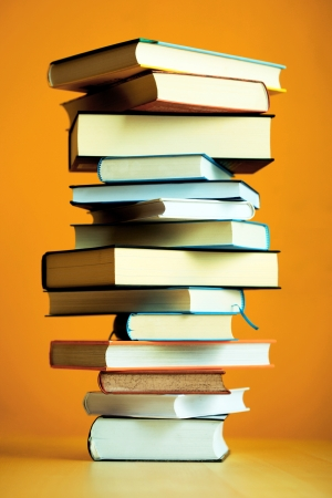 learned: Stack of Books Resembling a Pillar on a Table Before Orange Wall Stock Photo