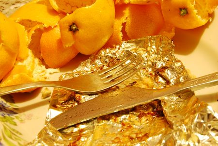 skins: Plate with used foil dirty fork and knife and skins of tangerine mandarin after meal