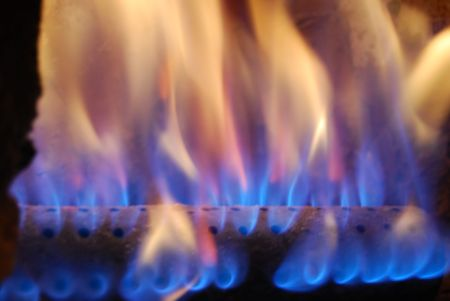 gas fireplace: Flames of blue and orange natural fire in warm gas furnace or fireplace Stock Photo