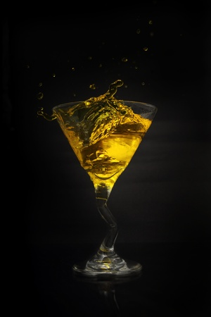 martini drink splash gold isolated on black background photo