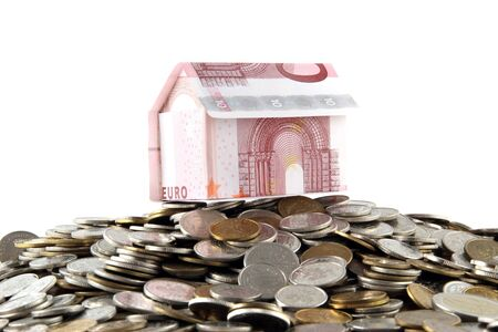 house built with euro coins and banknotes on white background photo
