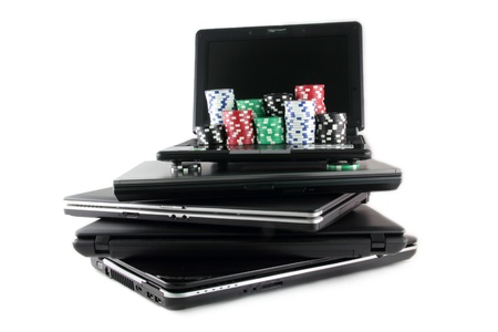 Online gaming and gambling concept, laptop and casino chips on keyboard Stock Photo