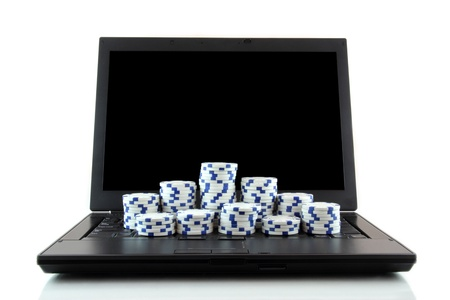Online gaming and gambling concept, laptop and white casino chips on keyboard photo