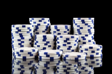 stack of white casino gambling chips on black background photo