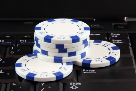 stack of white casino gambling chips on keyboard, online gaming concept photo