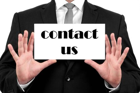 Contact Us  Businessman in black suit and a white shirt with a black tie, shows business card photo
