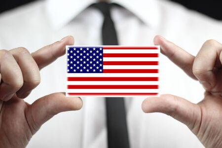 Businessman holding a business card with a USA Flag photo