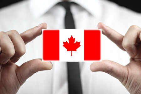 Businessman holding a business card with a Canada Flag photo