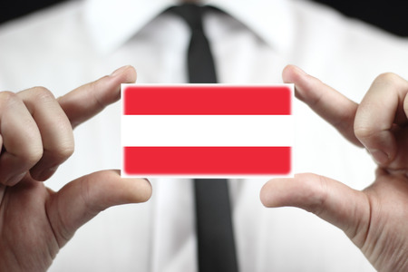 Businessman holding a business card with a Austria Flag photo