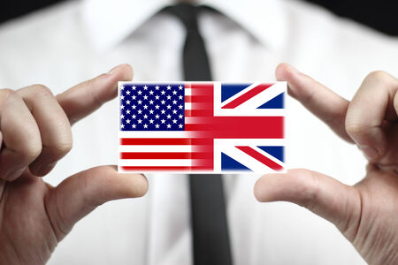 Businessman holding a business card with USA and UK Flag photo