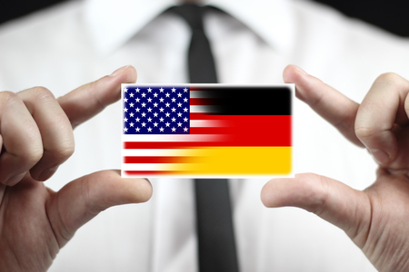 wiretapping: Businessman holding a business card with USA and Germany Flag