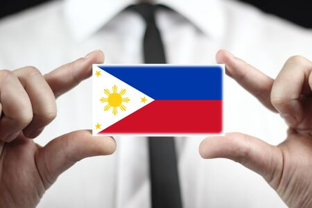 Businessman holding a business card with Philippines Flag photo