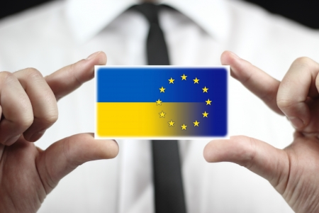 eu: Businessman holding a business card with EU and Ukraine Flag