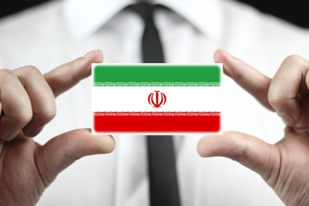 Businessman holding a business card with Iran Flag Stock Photo