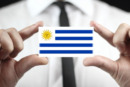 Businessman holding a business card with Uruguay Flag