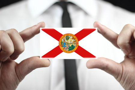 Businessman holding a business card with Florida Flag Stock Photo
