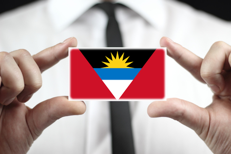 antigua: Businessman holding a business card with Antigua and Barbuda Flag