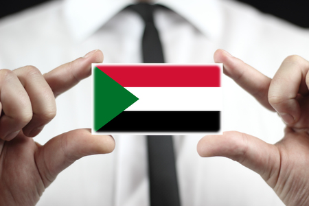 sudan: Businessman holding a business card with Sudan Flag